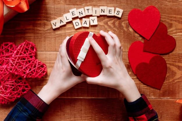 De handen van een tiener openen een valentijnsdag geschenk op een houten achtergrond. harten en vakantiedecor op tafel. Premium Foto