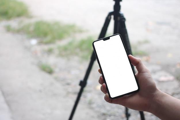 De handen van een zakenman die een lege smartphone houden en hebben exemplaarruimte. Premium Foto