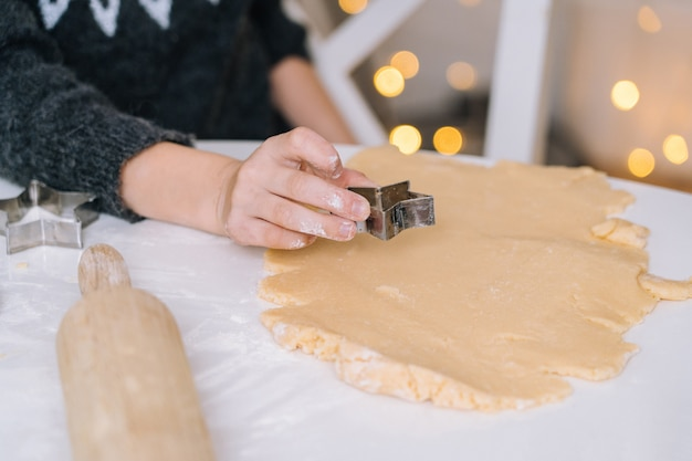 De handen van het close-upkind die koekjes voorbereiden die koekjessnijders gebruiken. Premium Foto