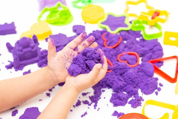 De handen van kinderen spelen kinetisch zand in quarantaine. paars zand op een witte tafel. coronapandemie Premium Foto