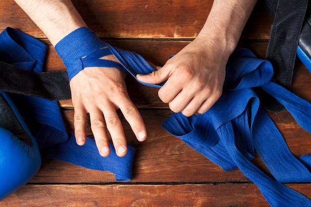 De handen van mannen tijdens het tapen voor een bokswedstrijd tegen een houten oppervlak. het concept van training voor bokstraining of vechten. plat lag, bovenaanzicht Premium Foto