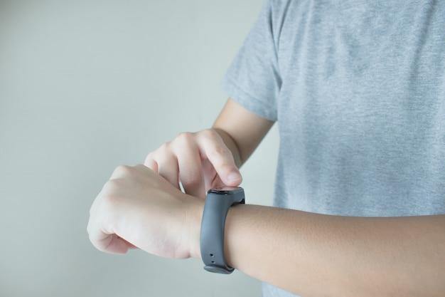 De handen van mensen die grijze t-shirts dragen, gebruiken intelligente horloges om de hartslag te volgen. Premium Foto