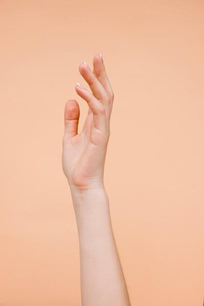 De handen van sideviewvrouw met lichtoranje achtergrond Gratis Foto