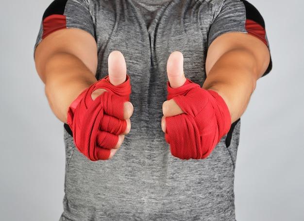 De handen van sportman gewikkeld in rood elastisch sportverband vertonen een soortgelijk teken Premium Foto