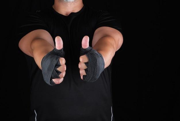 De handen van sportman gewikkeld in zwart elastisch sportverband vertonen een soortgelijk teken Premium Foto