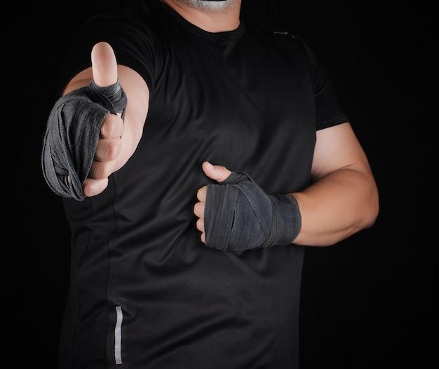 De handen van sportman gewikkeld in zwart elastisch sportverband vertonen een soortgelijke indruk Premium Foto