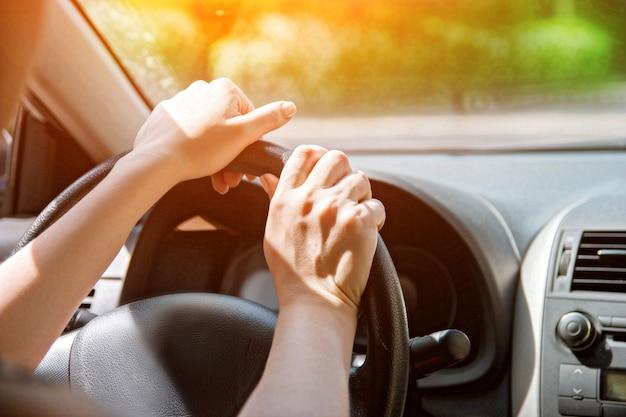 De handen van vrouwen aan het stuur. detailopname Premium Foto