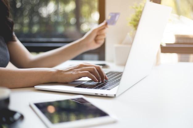 De handen van vrouwen bevatten creditcards en kopen online via laptops. Premium Foto