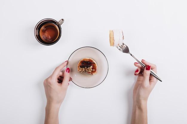 De handen van vrouwen met een rode manicure vastgemaakt op een vork fluitje van een cent Premium Foto