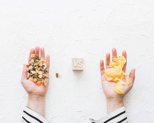 De handholding van het wijfje dryfruits tegenover aardappels spaanders op geweven achtergrond Gratis Foto