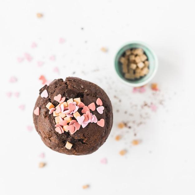 De hartvorm bestrooit over cupcake op witte achtergrond Gratis Foto