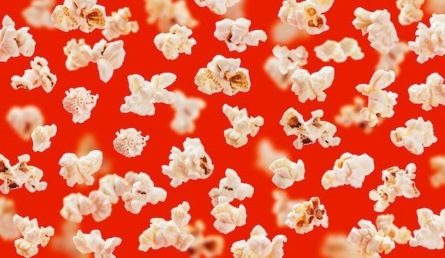 De heerlijke close-up van pop graankorrels op rode achtergrond Premium Foto