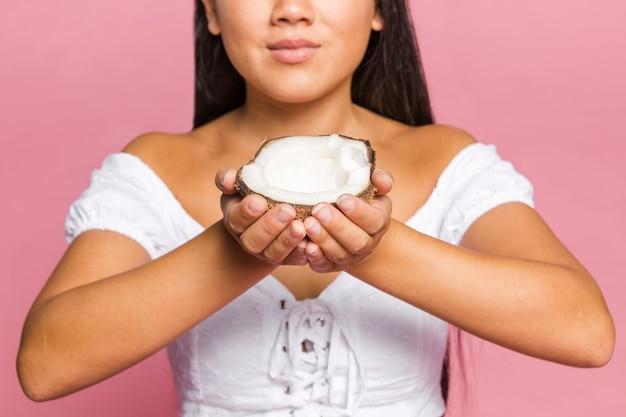 De helft van de kokosnoot wordt vastgehouden door de vrouw Gratis Foto