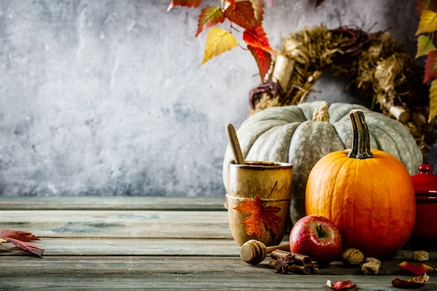 De herfstachtergrond op houten tabel tegen de oude uitstekende muur van de roestvoorwaarde Premium Foto