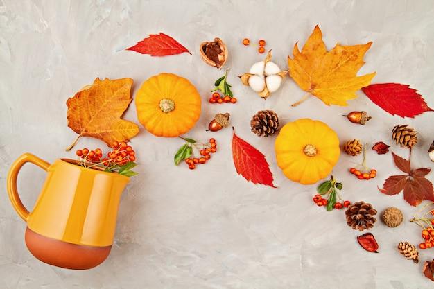 De herfstbladeren, pompoenen, bessen gieten uit een waterkruik op een grijze achtergrond Premium Foto