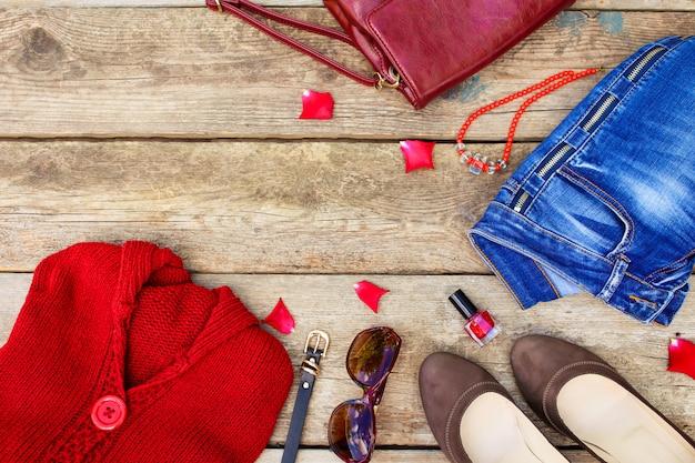 De herfstkleding van vrouwen en toebehoren rode sweater, jeans, handtas, parels, zonnebril, nagellak, schoenen, riem op houten achtergrond. bovenaanzicht. Premium Foto
