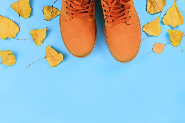 De herfstlaarzen van oranje bruine mensen op blauwe pastelkleurachtergrond. bovenaanzicht, kopie ruimte. Premium Foto