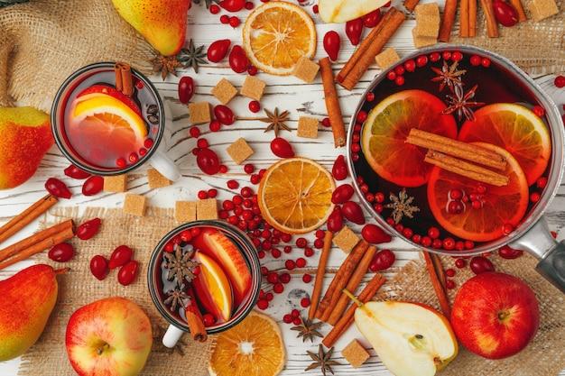 De herfstsamenstelling met hete overwogen wijn en kruiden op houten achtergrond Premium Foto