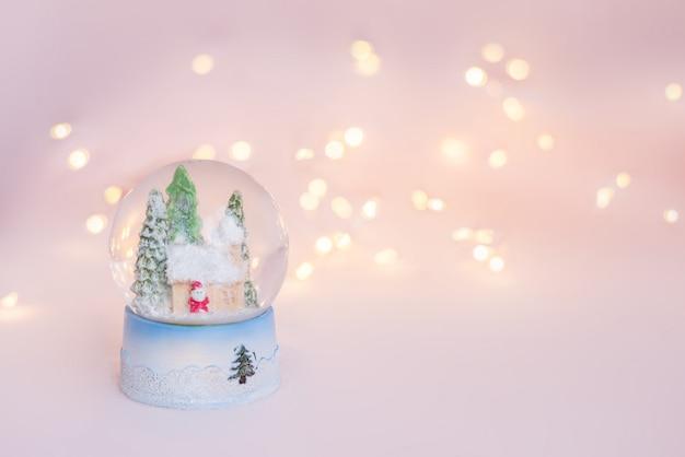 De herinnering van de de sneeuwbol van de gift op een lichtrose achtergrond met kerstmislichten Premium Foto