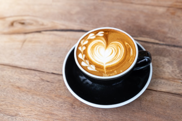De hete cappuccino van de kunstkoffie in een kop op houten lijstachtergrond met exemplaarruimte Gratis Foto