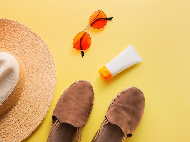 De hoed van de strovrouw met zonglazen, beschermingsroom en van sandals hoogste mening heldere gele vlakke achtergrond. Premium Foto