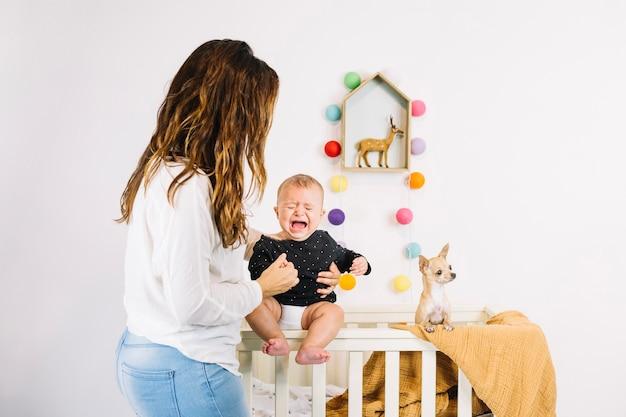 De holdings huilende baby van de vrouw dichtbij hond Premium Foto
