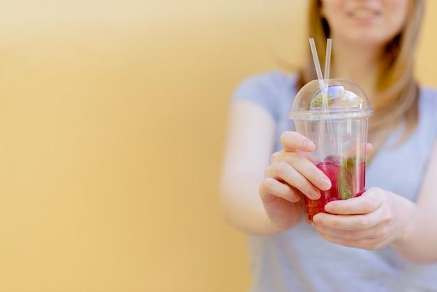 De holdings smoothie van de vrouwenhand schok tegen gekleurde muur. Premium Foto