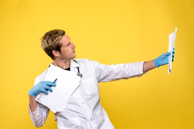 De holdingsanalyses van de vooraanzicht mannelijke arts op de gele gezondheid van het medicziekenhuis Gratis Foto