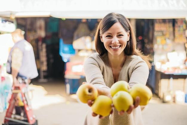 De holdingsappelen van de vrouwenklant bij groene markt. Premium Foto