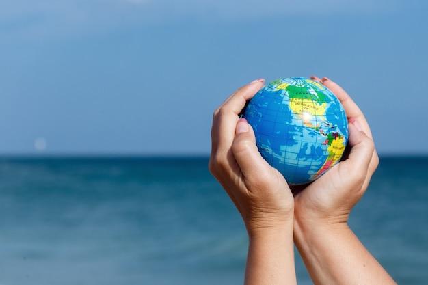 De holdingsbol van de vrouw van de aarde op een achtergrond van het overzees. Premium Foto