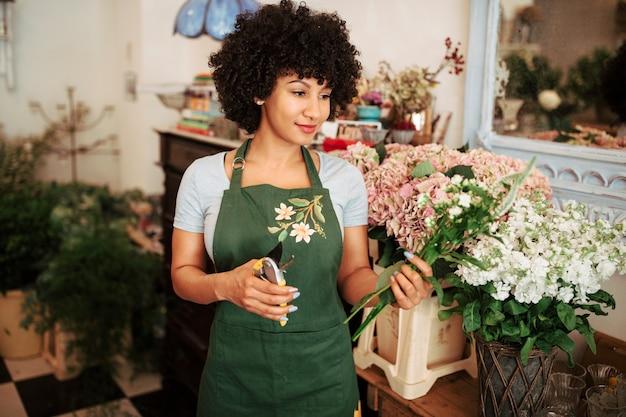 De holdingsbos van de vrouw van bloemen in winkel Gratis Foto