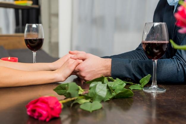 De holdingshanden van de man met vrouw bij lijst met glazen en bloei Gratis Foto