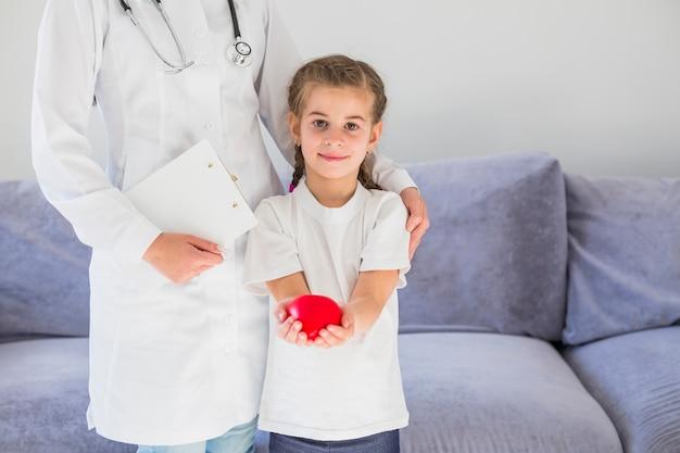 De holdingshart van het blondemeisje met arts Gratis Foto
