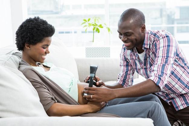 De holdingshoofdtelefoons van de man op de maag van de zwangere vrouw in woonkamer Premium Foto