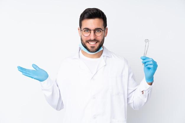 De holdingshulpmiddelen van de tandartermens op witte muur die lege ruimte op de palm houden Premium Foto