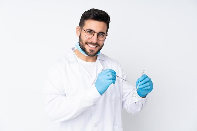 De holdingshulpmiddelen van de tandartermens op witte muur Premium Foto