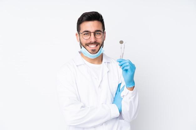 De holdingshulpmiddelen van de tandartsmens bij het witte muur lachen worden geïsoleerd die Premium Foto