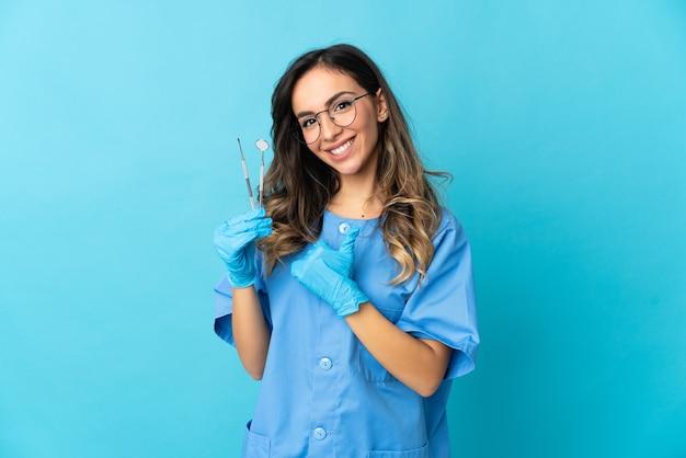De holdingshulpmiddelen van de vrouwentandarts over geïsoleerd op blauwe muur die een duim omhoog gebaar geven Premium Foto