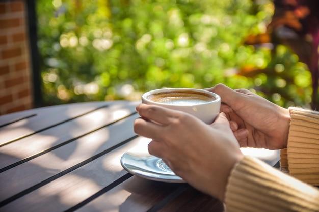 De holdingskop van de persoon van koffie op houten lijst Premium Foto