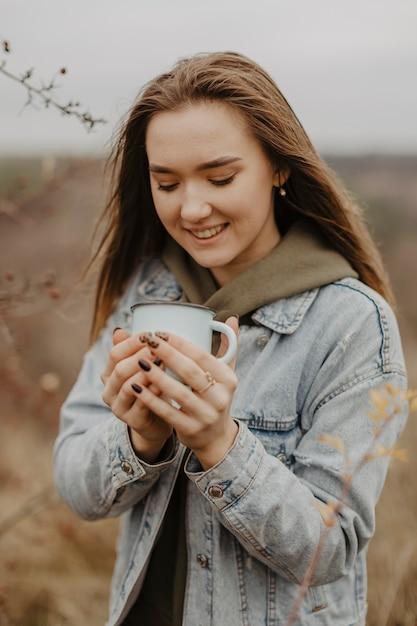 De holdingskop van de portret jonge vrouw met thee Gratis Foto