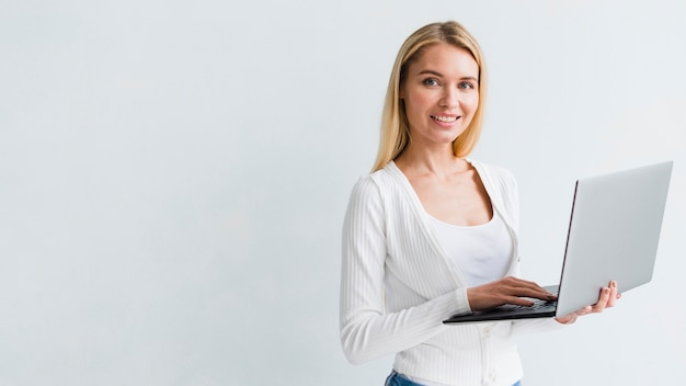 De holdingslaptop van de blondewerknemer op witte achtergrond Gratis Foto