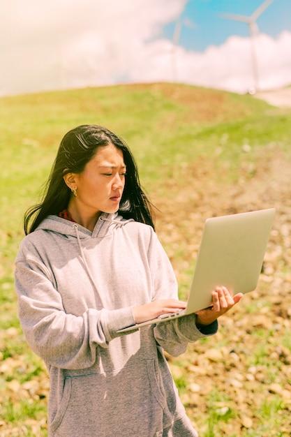 De holdingsnotitieboekje van de vrouw en status op achtergrond van heuvels Gratis Foto