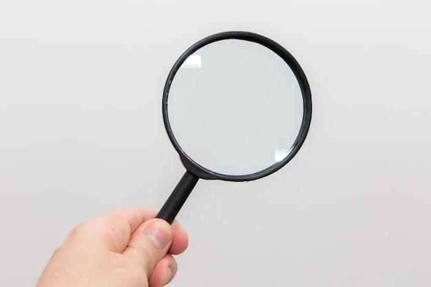 De holdingsvergrootglas van de hand op witte achtergrond Premium Foto