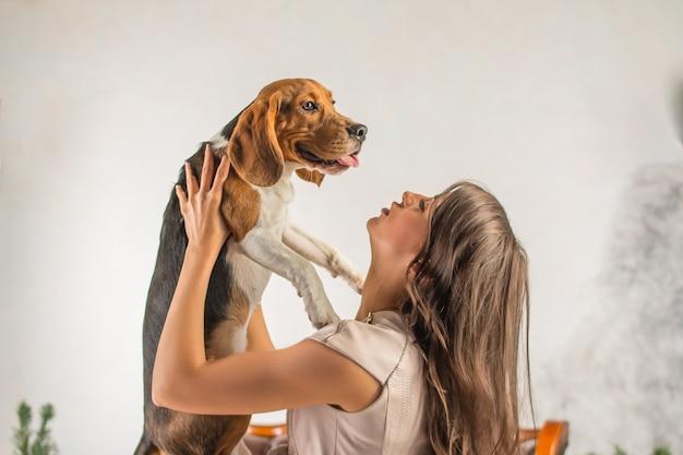 De hond is in handen van de minnares. meisje speelt met hond. leuke beagle ontspannen. ze hebben plezier samen. jonge vrouw die haar hond clutching Premium Foto