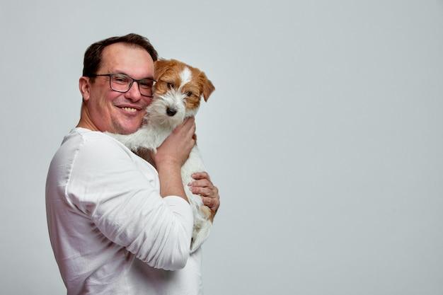 De hond ligt op de schouder van zijn baasje. jack russell terrier in handen van zijn eigenaar op witte muur. het concept van mensen en dieren. t Premium Foto