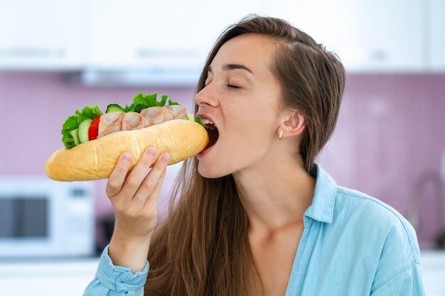 De hongerige vrouw eet eigengemaakte sandwich. voedselverslaving. vraatzucht en overgewicht door ongezond eten Premium Foto