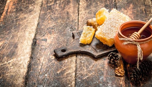 De honing in de pot met de noten en kegels op houten tafel. Premium Foto