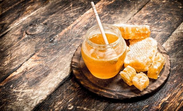 De honing in de pot met de noten op houten tafel. Premium Foto