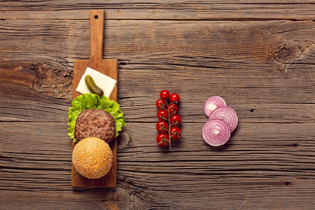 De hoogste ingrediënten van de meningshamburger op houten lijst Gratis Foto