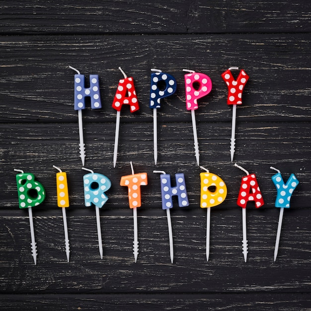 De hoogste kaarsen van de meningsverjaardag op houten achtergrond Gratis Foto
